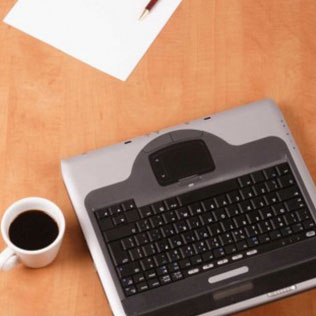 cup of coffee, sheet of paper, pen, and keyboard on a desk