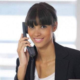 smiling woman dressed in business attire on a phone