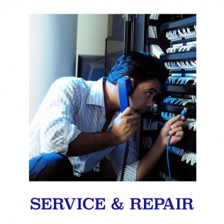 man with a blue phone to his ear adjusting telecom equipment